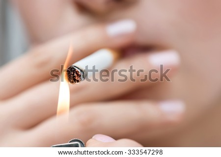 Give me fire. Close up of cigarette in hands of unhealthy girl lighting it and smoking - stock photo