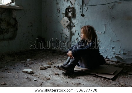 Give me support. Poor depressed little girl folding her legs and sitting on the floor while looking up - stock photo