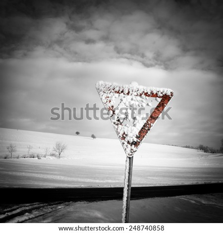 give way road sign , traffic sign, yield sign, with blue sky and clouds and with snow in winter season - stock photo