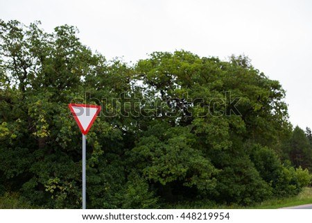 Give way traffic sign on a forest background - stock photo