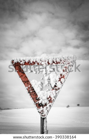 give way traffic sign, traffic sign, yield sign, with blue sky and clouds and with snow in winter season - stock photo