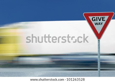 Give way yield road traffic sign and motion blurred truck in the background, blue sky - stock photo