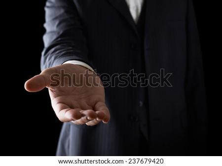 Giving a helping hand, asking or offering help close-up shot of a caucasian man in a business suit, low-key dramatic light composition - stock photo