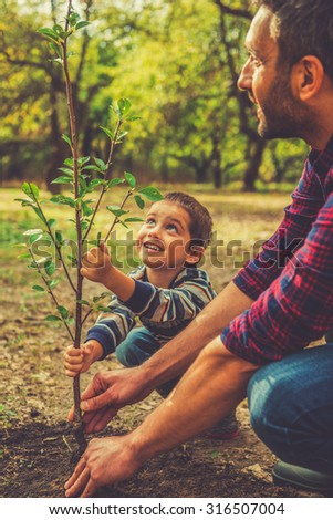 Giving a new life. Cheerful little boy helping his father to plant the tree while working together in the garden - stock photo