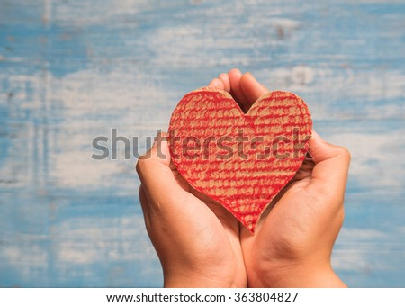 Giving and Take Red Crate paper heart by hand.Focus on Heart.