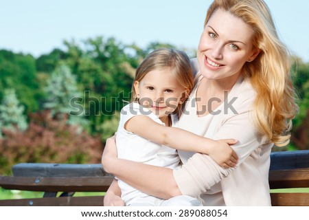 Giving care. Young attractive mother sitting in park and holding her little cute daughter  - stock photo