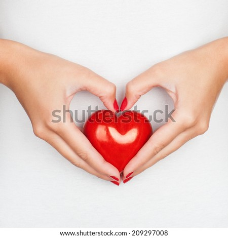 Giving love concept with hands holding a red heart. - stock photo