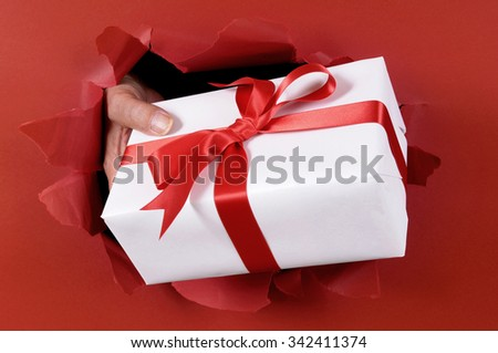Giving or delivering Christmas gift through torn red paper background.