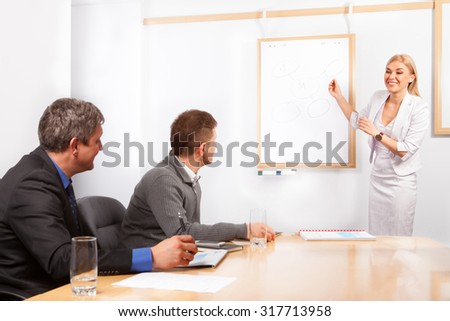 Giving presentation young executive during meeting woman pointing flip chart - stock photo