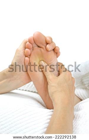 Giving Reflexology Treatment - Reflexologist holding patient's foot applying pressure to the solar plexus region - stock photo