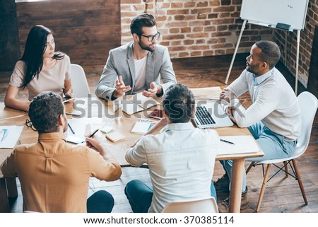 Giving some advises to coworkers. Top view of young business people discussing something while sitting at the office desk together - stock photo