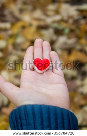 giving the child's heart in the palm of the hand - stock photo