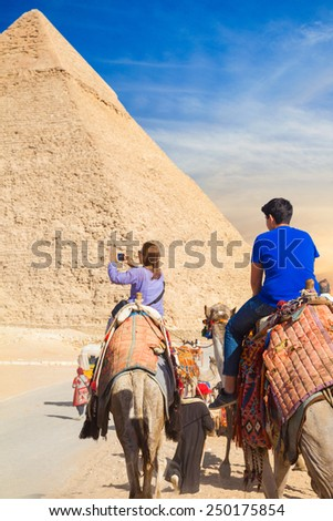 GIZA, EGYPT - JAN 31, 2015: Girl rides a camel at Giza Necropolis and take photo on smartphone - stock photo
