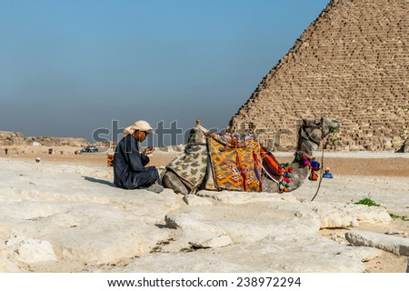 GIZA, EGYPT - NOV 23, 2014: Unidentified Egyptian man and his camel at Giza Necropolis, Egypt. UNESCO World Heritage - stock photo