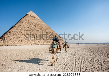 GIZA, EGYPT - NOV 23, 2014: Unidentified Egyptian people on camels caravan near the Great Pyramid in  Giza Necropolis, Egypt. UNESCO World Heritage - stock photo