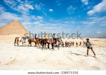 GIZA, EGYPT - NOV 23, 2014: Unidentified tourists and local horse and camel riders in Giza Necropolis, Egypt. UNESCO World Heritage