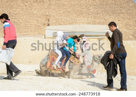 GIZA, EGYPT - NOV 23, 2014: Unidentified tourists ride a camel at Giza Necropolis, Egypt. UNESCO World Heritage - stock photo