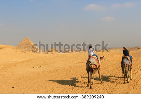 GIZA PYRAMIDS, EGYPT - JANUARY 31, 2016: Women ride camels on the golden desert sands near the Pyramids of Giza in Egypt  - stock photo