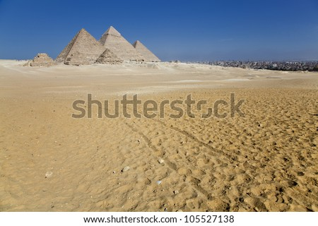 Giza pyramids with the background of the city - stock photo