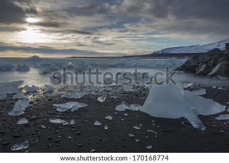 Glacial ice on black sand - stock photo