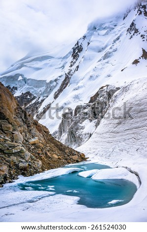 Glacial lake in the mountains of Caucasia. Too much snow and ice. Picture was taken during a trekking hike in the scenic and beautiful  Caucasus mountains, Bezengi region, Kabardino-Balkaria, Russia - stock photo