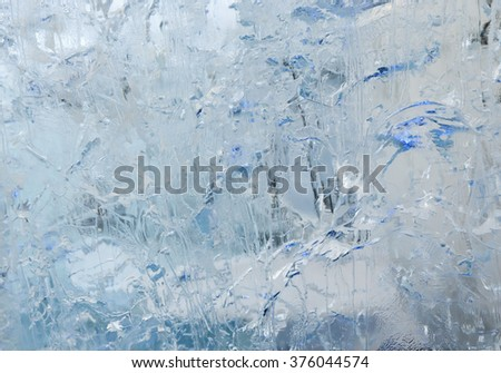 Glacial transparent wall of ice with interesting drawings and patterns. Winter background.