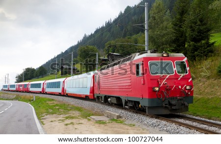 Glacier express train passes high mountain valley, Switzerland - stock photo