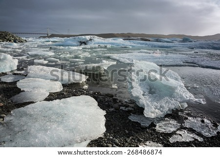 Glacier ice lagoon in Jokullsarlon, Iceland. The glacier breaks up into ice blocks in the lagoon before flowing out to sea as icebergs. - stock photo