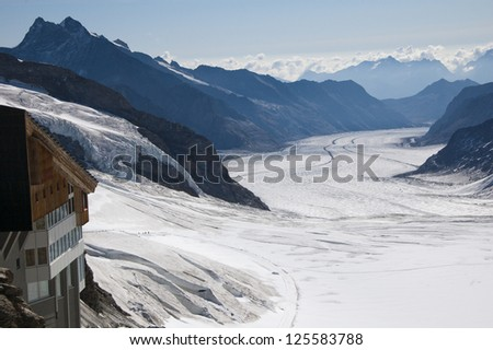 Glacier in Swiss Alps from Jungfraujoch and building - stock photo