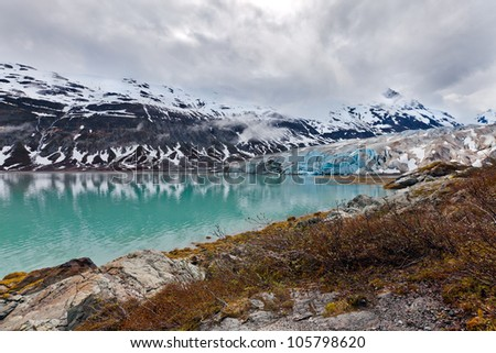 Glacier landscape in Alaska with blue ice reflected in a lake of glacial melt. Glacier Bay wilderness. - stock photo