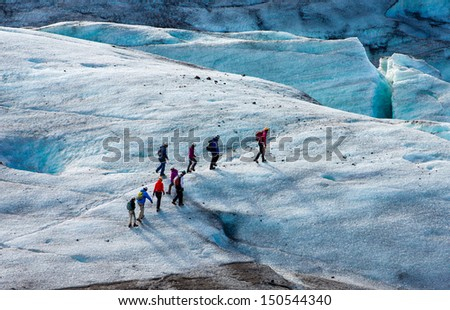 Glacier trekkers walk along a Vatnajokull Iceland - stock photo