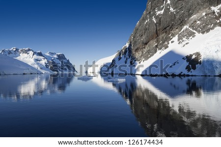 Glaciers and icebergs of Antarctic Peninsula. Travel on deep pure waters among ices of Antarctica. Fantastic snow landscapes. - stock photo