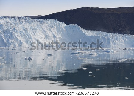 Glaciers of Greenland. Icebergs of different forms in the gulf. Studying of a phenomenon of global warming and catastrophic thawing of ices.