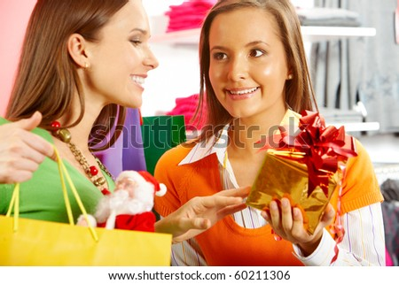 Glad customer looking at wrapped gift being offered to her by helpful shop assistant - stock photo