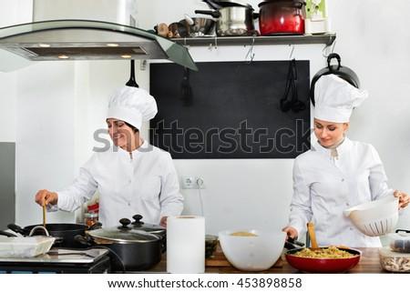 Glad diligent friendly  female chefs preparing food on restaurant kitchen - stock photo