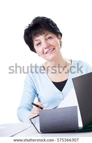Glad elderly woman doing paperwork at office
