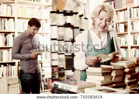 Glad elderly woman reading book while choosing it in book shop