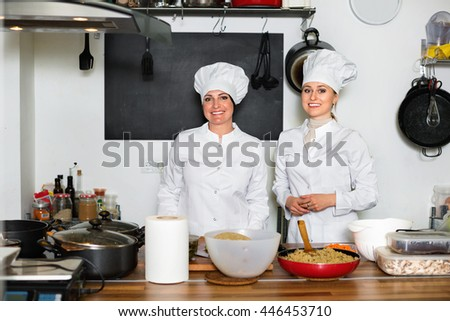 Glad female chefs preparing food on restaurant kitchen - stock photo