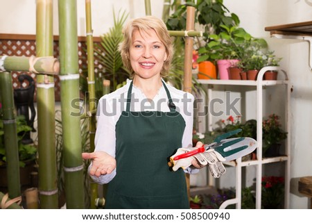 Glad female florist wearing an apron and happily standing amongst plants with tools in floral shop