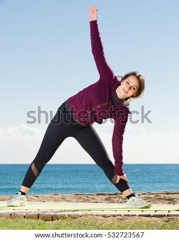 Glad girl exercising on exercise mat outdoor
