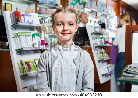 Glad girl holding a product box in the pharmacy with parents and pharmacist on the background