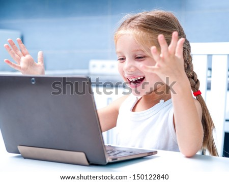 glad little girl with her computer at home at the table - stock photo