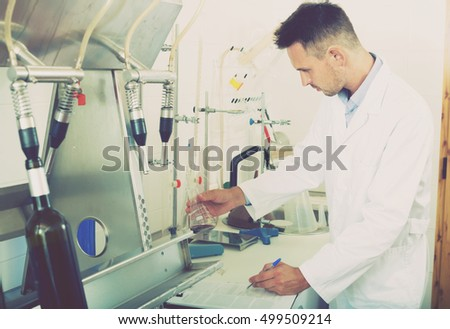 Glad man in white coat working on quality of products in winery lab