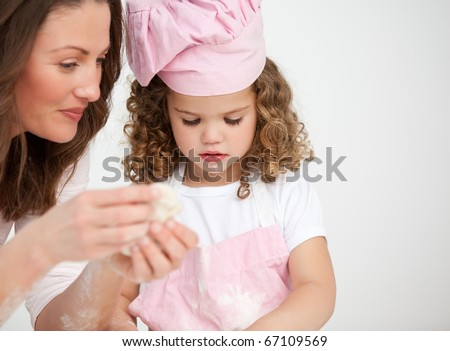 Glad mother and her daughter making biscuits together in the kitchen - stock photo