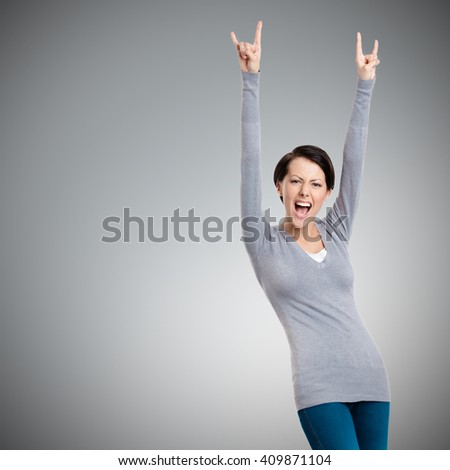 Glad pretty woman puts her hands up, isolated on grey - stock photo