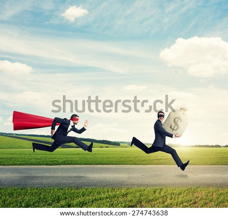 glad thief stole the bag with money and running away from superman on the road at outdoor - stock photo