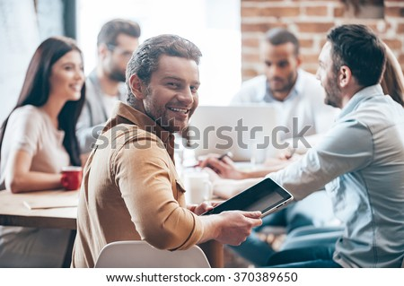 Glad to be a part of team. Cheerful young man holding digital tablet and looking at camera while his colleagues discussing something in the background  - stock photo