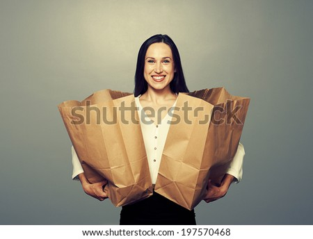 glad woman holding paper bags over dark background - stock photo