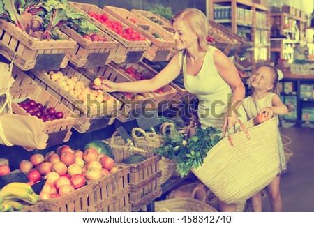 Glad young mother with daughter shopping a various fruits in food store - stock photo