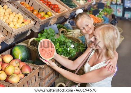 Glad young mother with daughter shopping various fruits in food store. Focus on woman  - stock photo